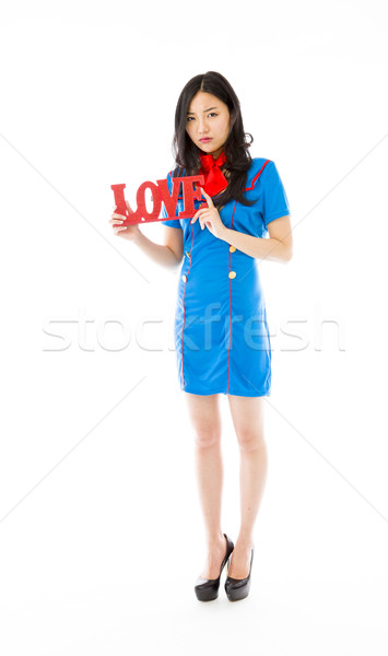 Disappointed Asian air stewardess holding red 'LOVE' text Stock photo © bmonteny
