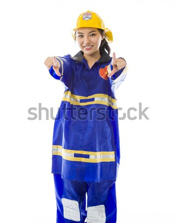 Stock photo: Lady firefighter pointing at you from both hands isolated on white background