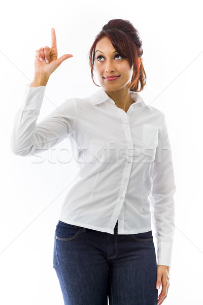 Indian young woman pointing upwards and looking at tip of finger Stock photo © bmonteny