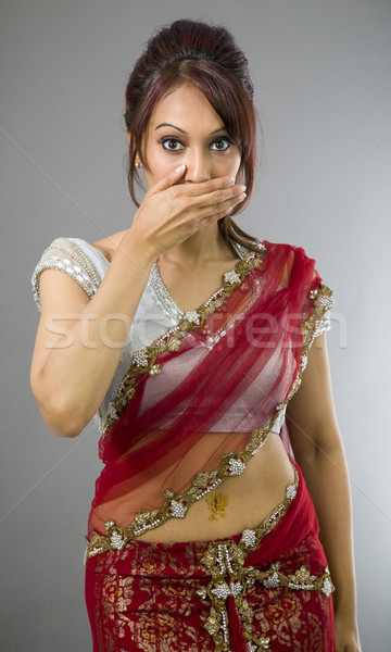 Young Indian woman with hand over her mouth Stock photo © bmonteny