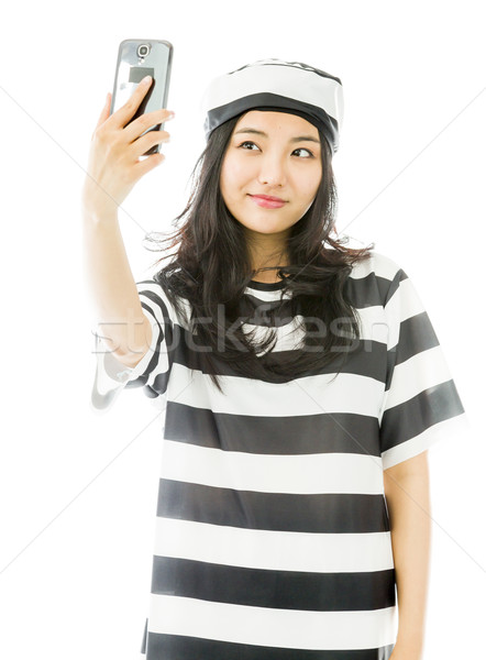 Asian young woman photographing herself with her mobile phone in prisoners uniform Stock photo © bmonteny