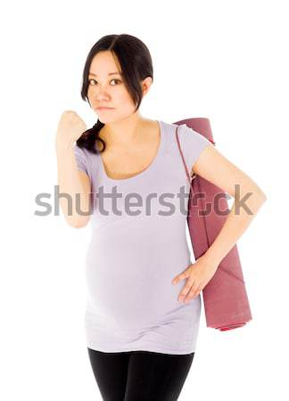 Young woman carrying exercising mat with hand over her mouth Stock photo © bmonteny