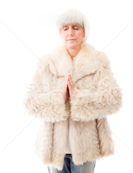 Senior woman standing in prayer position Stock photo © bmonteny