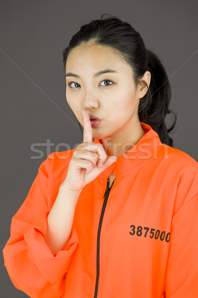 Young Asian woman with finger on lips in prisoners uniform Stock photo © bmonteny
