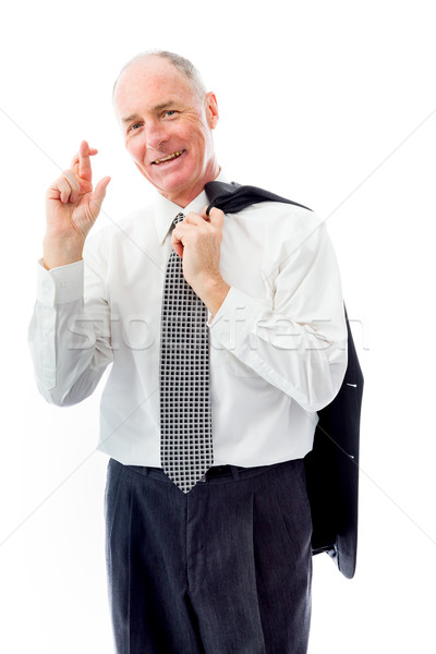 Businessman standing with finger crossed for luck Stock photo © bmonteny