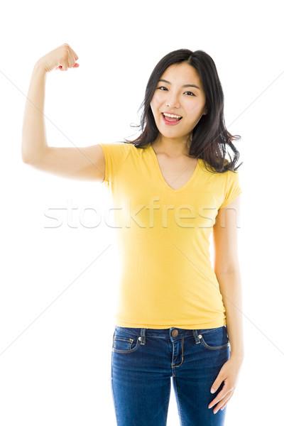 Fiatal ázsiai nő mutat el izom Stock fotó © bmonteny