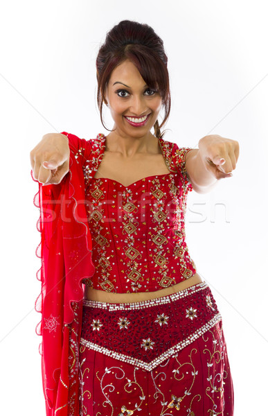 Smiling young Indian woman pointing towards camera from both hands Stock photo © bmonteny