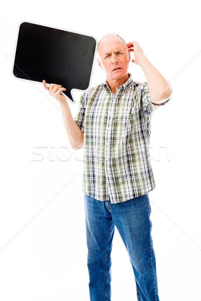 Senior man holding a blank speech bubble and thinking Stock photo © bmonteny