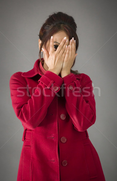 Shy Indian young woman peeking through covered face isolated on colored background Stock photo © bmonteny