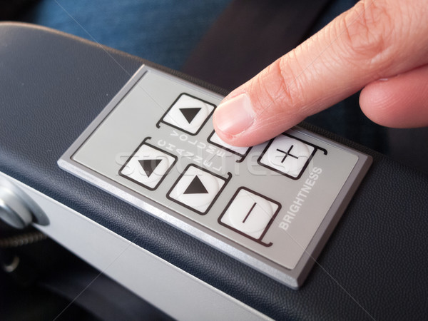 Human finger pressing push buttons on the armrest of airplane se Stock photo © bmonteny