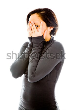 Young woman peeking through hands covering face Stock photo © bmonteny