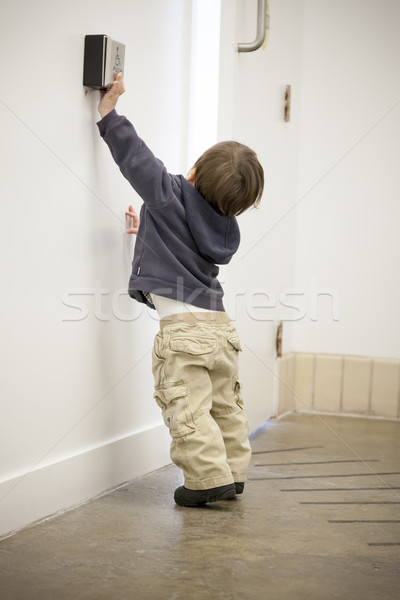 Stock photo: Boy using a card key to open a door