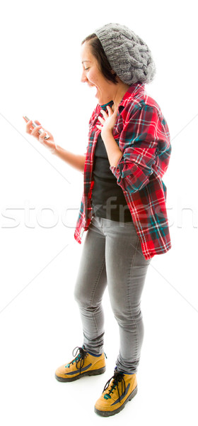 Young woman text messaging on mobile phone and looking surprised Stock photo © bmonteny
