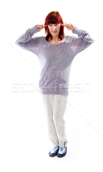 Stock photo: Mature woman standing with fingers in her ears