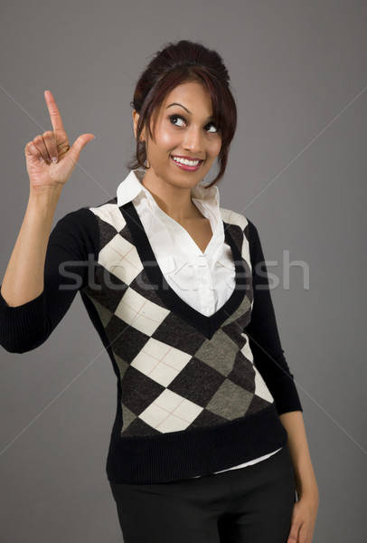 Indian businesswoman smiling and pointing upwards Stock photo © bmonteny