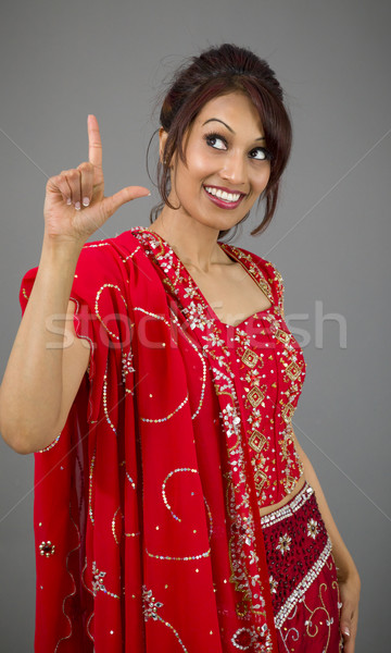 Young Indian woman pointing upward and smiling Stock photo © bmonteny