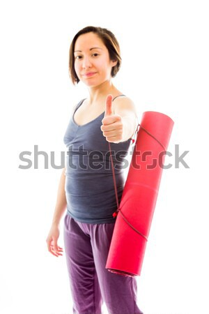 Young woman carrying exercise mat wishing with crossing fingers Stock photo © bmonteny