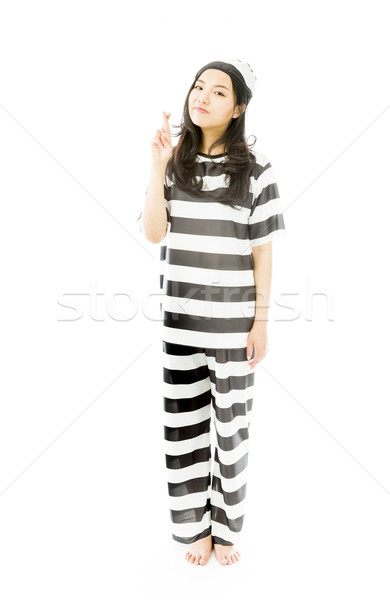 Young Asian woman in prisoners uniform standing with finger crossed Stock photo © bmonteny