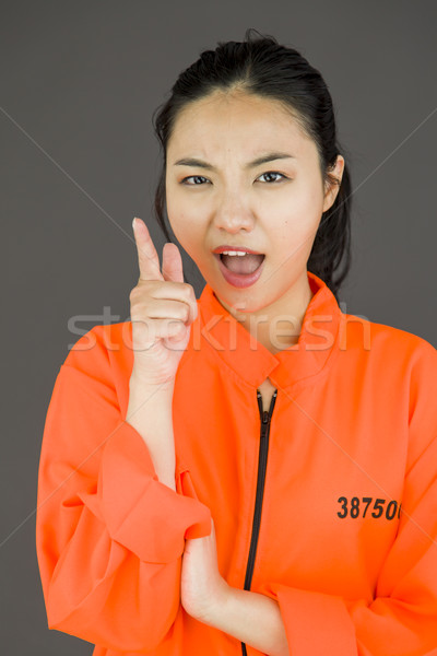 Young Asian woman scolding somebody in prisoners uniform Stock photo © bmonteny