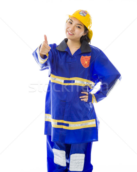 Lady firefighter making thumbs up sign standing with hand on hip Stock photo © bmonteny