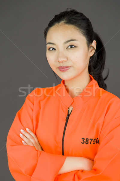 Young Asian woman with her arms crossed in prisoners uniform Stock photo © bmonteny