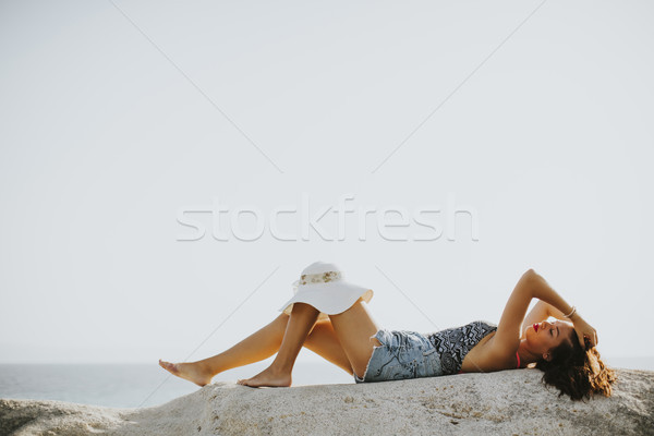 Pretty young woman on the stony beach Stock photo © boggy