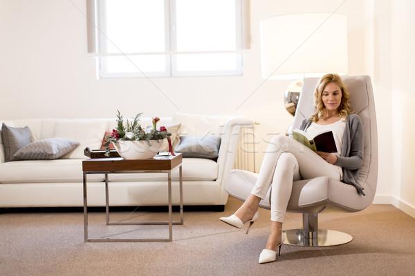 Vrouw lezing boek vergadering comfortabel stoel Stockfoto © boggy