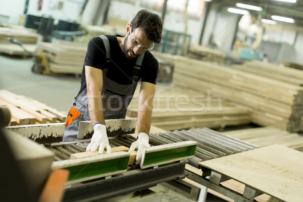 Young man works in a factory for the production of furniture Stock photo © boggy
