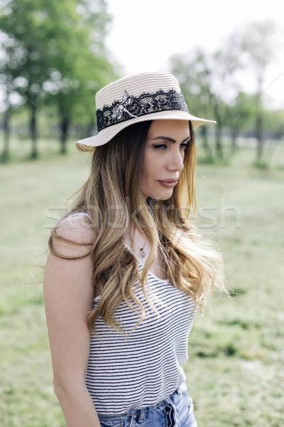 Portrait of a beautiful elegant woman with hat posing in the par Stock photo © boggy