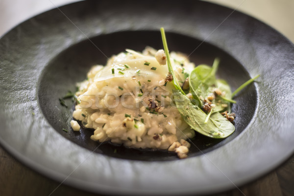 Risotto with gem fit and levisticum celery on a wood table compo Stock photo © boggy