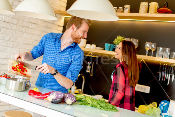 Young couple have fun in modern kitchen indoor while preparing v Stock photo © boggy