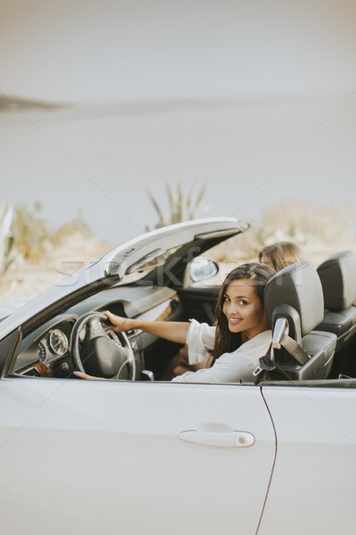 Two happy friends in white cabriolet car driving everywhere Stock photo © boggy