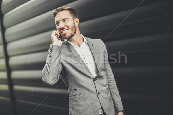 Handsome young man with mobile phone by the office building Stock photo © boggy