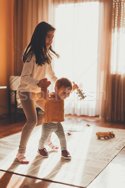 Little girl helping baby sister to walk Stock photo © boggy
