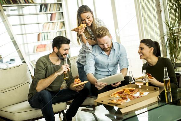 Młodych ludzi jedzenie pizza pitnej jabłecznik oglądania Zdjęcia stock © boggy