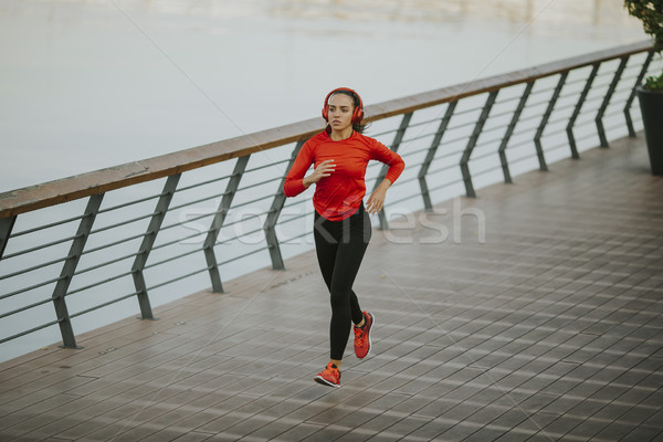 Active young beautiful woman running in urban enviroment Stock photo © boggy