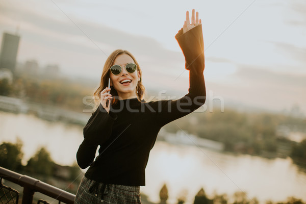 Young woman holding mobile phone while standing on walkway by th Stock photo © boggy