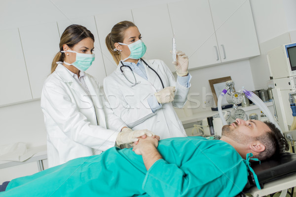 Female doctors preparing patient for intervention Stock photo © boggy
