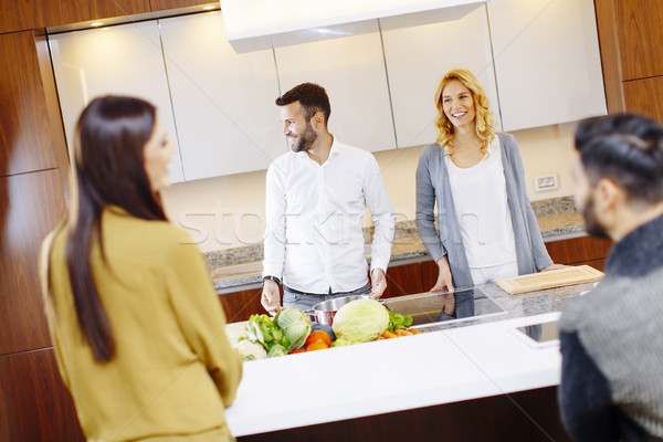 Group of young men and women cooking together at home in modern  Stock photo © boggy