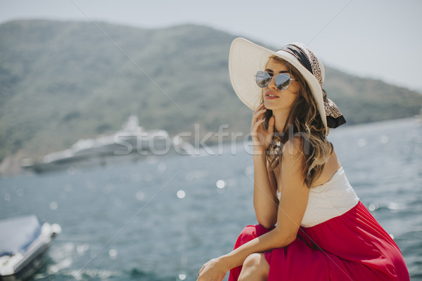Stock photo: Pretty young woman sitting by the sea