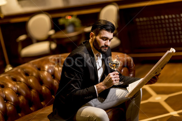 Handsome man drinking white wine and reading newspaper Stock photo © boggy