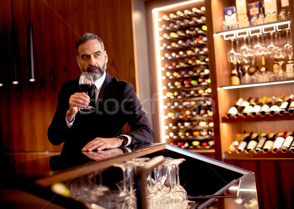 Portrait of handsome elegant businessman drinking red wine in ba Stock photo © boggy