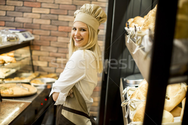 Young woman posing in front of shelves in  baker shop Stock photo © boggy