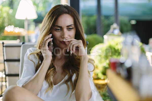 Young woman sitting in cafe and using mobile phone Stock photo © boggy