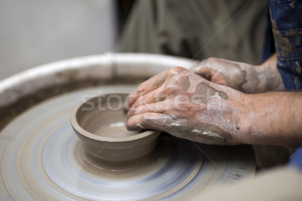 Artist makes clay pottery on a spin wheel Stock photo © boggy