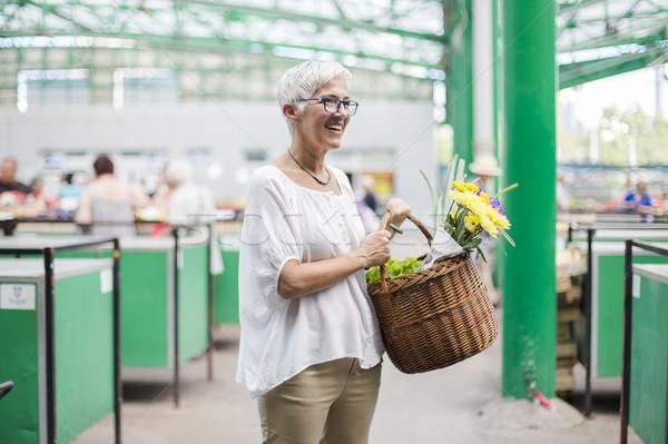 Idős nő tart kosár virágcsokor virágok Stock fotó © boggy