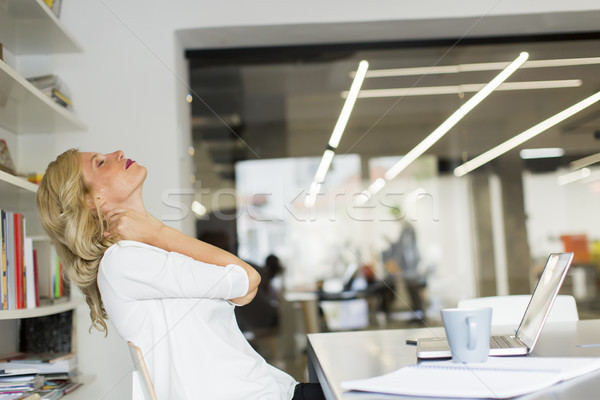 Businesswoman in the office taking a break and doing a neck exer Stock photo © boggy