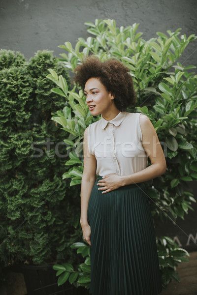 Curly hair young woman standing in the courtyard Stock photo © boggy
