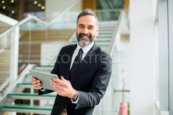 Middle age businessman with tablet in the office Stock photo © boggy