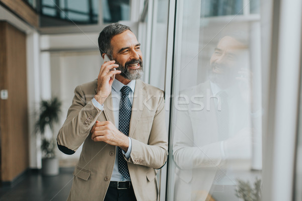 Handsome mature businessman  with mobile phone Stock photo © boggy